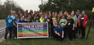 """Image of Youth with Banner Proclaiming """"Love is Love"""""""