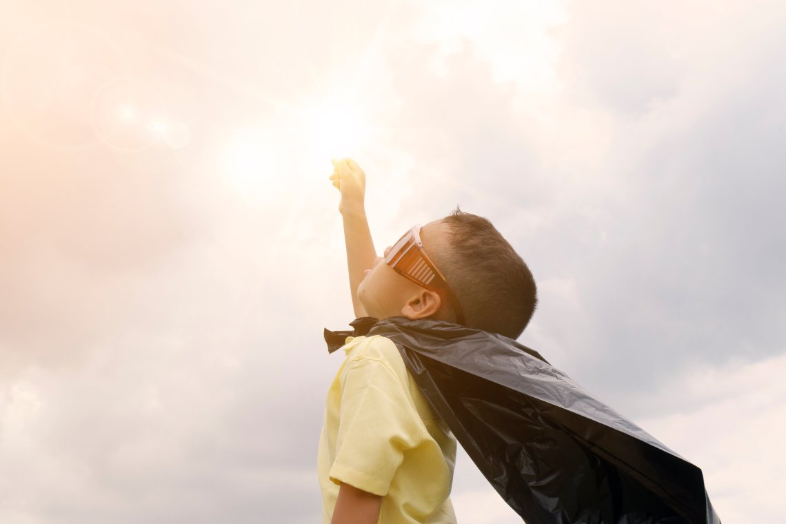 A child wearing sunglasses and a homemade cape, fist held high.