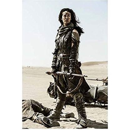 Courtney Eaton as Cheedo the Fragile holding a rifle as she stands over a body in Mad Max Fury Road