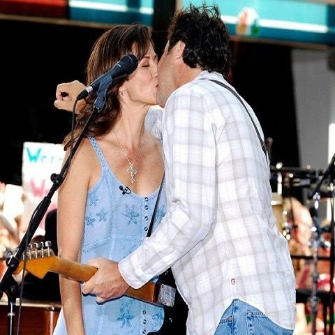 Amy Grant and her spouse Vince gill kissing during the show