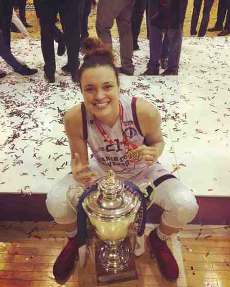 Photo of Kayle McBride is wearing a gold medal along with the Championship Trophy.