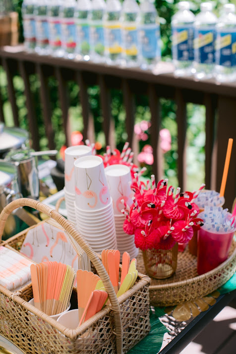 Rattan Tray and Tableware Organizers Full of Flamingo Plates, Napkins, Cups, and Colorful Disposable Wooden Cutlery.