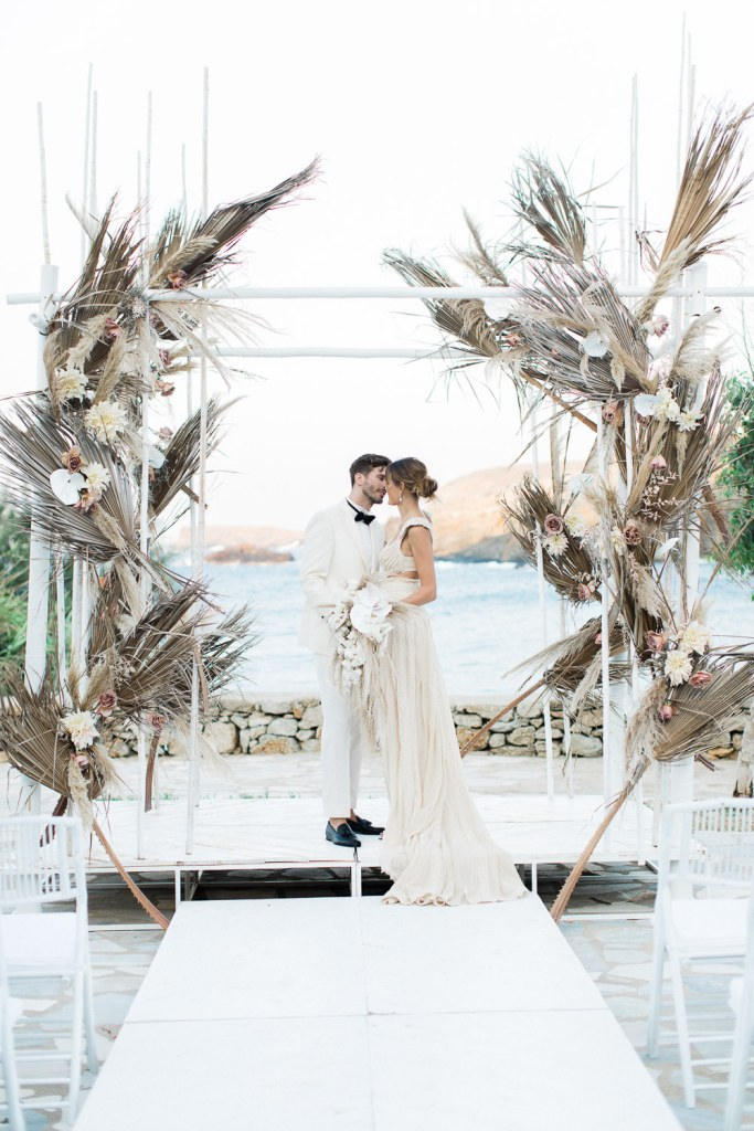 Couple at alter with natural decor elements like leaves and pampas grass