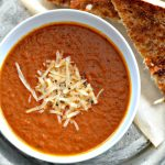 With healing bone broth, heavy cream, and fresh basil, this is THE best tomato basil soup ever! And you can make this simple soup, with nourishing bone broth and infused with parmesan rind, in less than 30 minutes.