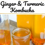 ginger turmeric kombucha in a glass with bottles behind the glass
