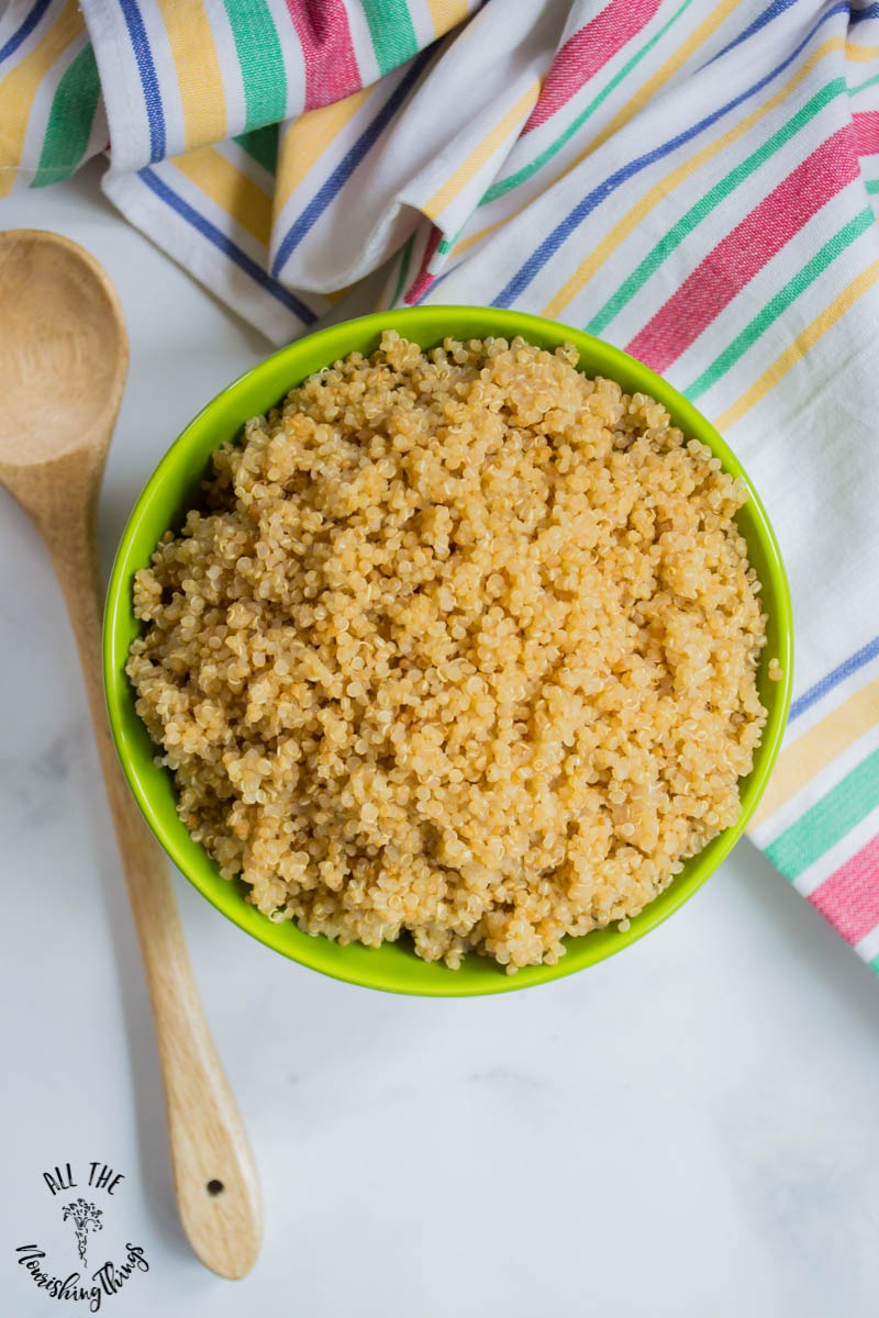 bowl of instant pot fluffy soaked quinoa with striped towel
