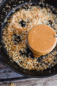jar of toasted coconut butter sitting in cast iron skillet with toasted coconut flakes