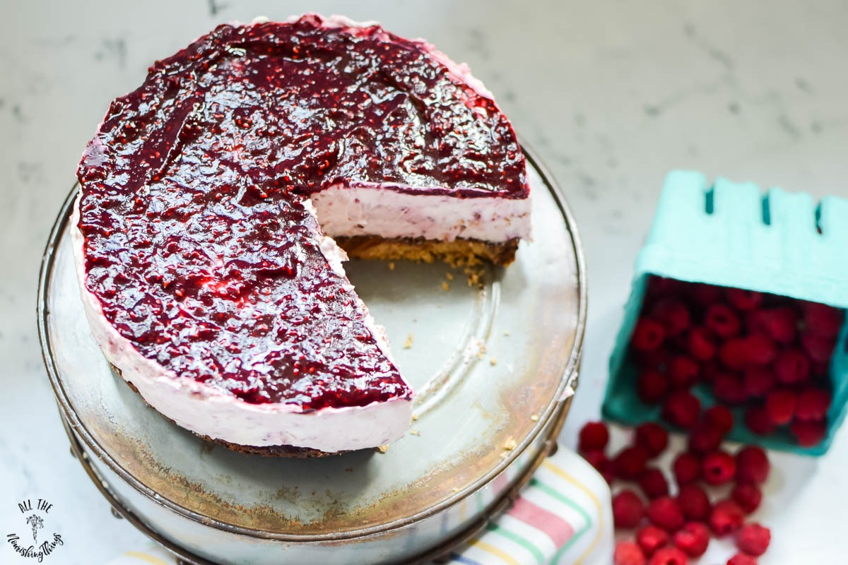 keto no-bake raspberry cheesecake on cake stand with slice cut out of it