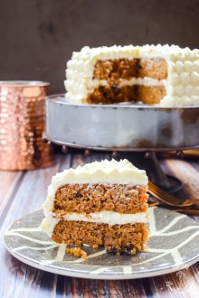 Keto Maple Carrot Cake on a plate with a copper cup and cake on a cake stand in the background.