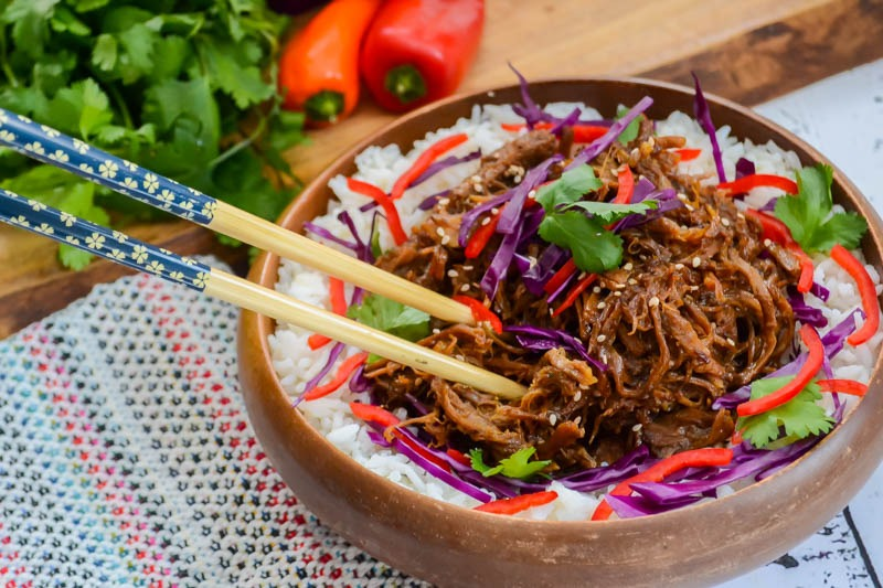wooden bowl of paleo instant pot sweet 'n spicy asian pulled pork with chopsticks