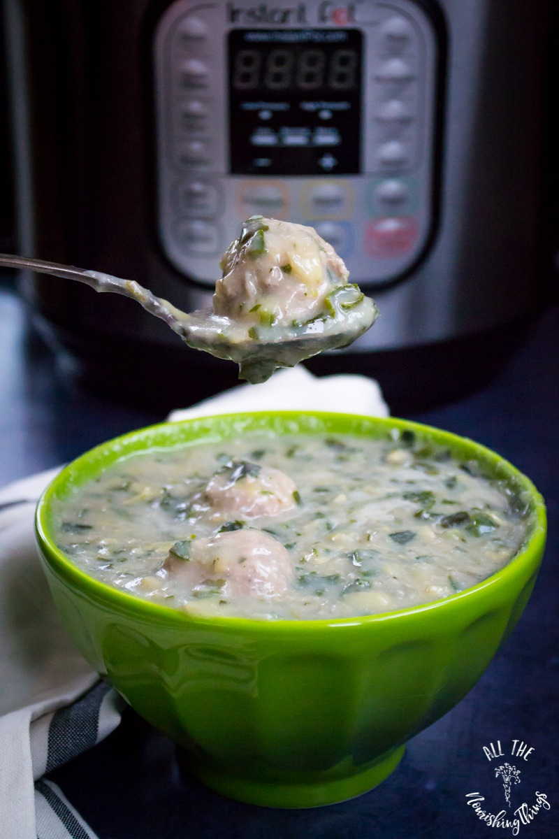 green bowl of instant pot spinach artichoke meatball soup with spoon holding a meatball above the bowl and instant pot in background
