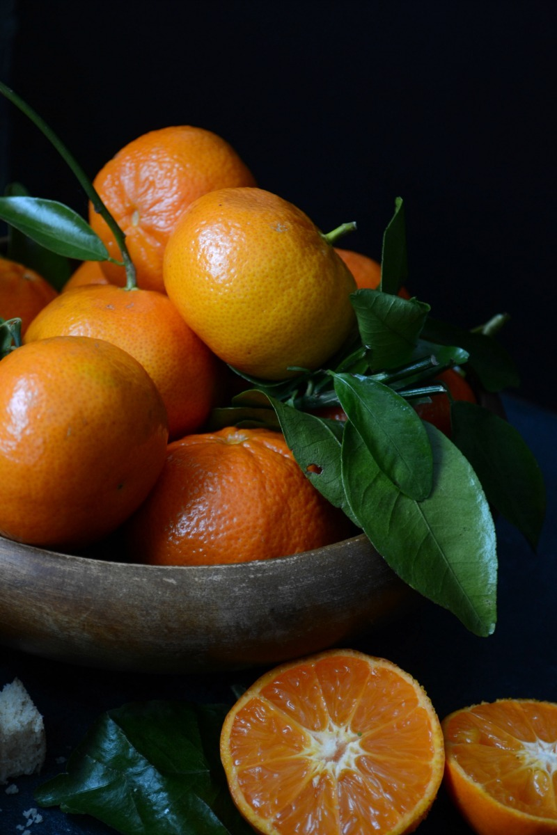 wooden bowl of mandarin oranges with leaves and stems