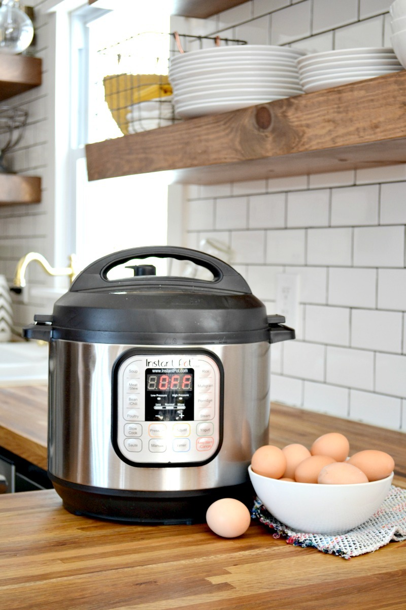 instant pot with boiled eggs on butcher block countertop