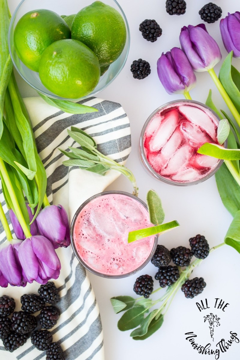 overhead shot of purple cocktails with limes and purple tulips
