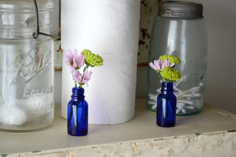 cobalt blue bottles with green and purple flowers sitting on shelf with cotton balls and toilet paper