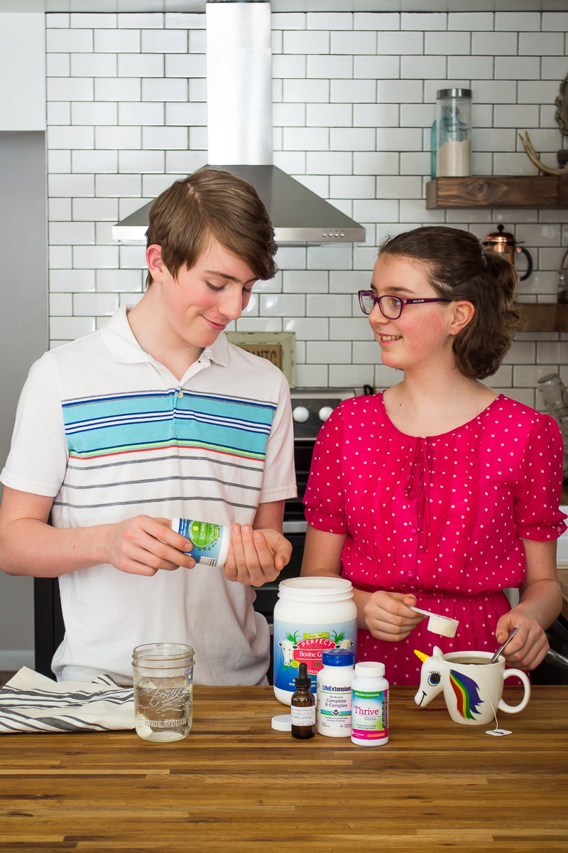 boy and girl taking supplements for teenagers in a kitchen