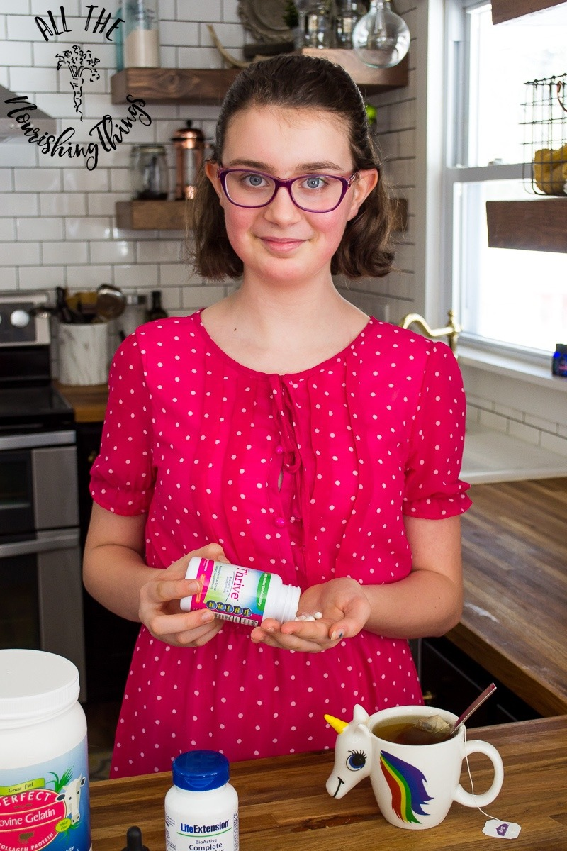 young girl wearing glasses and pink dress smiling and taking supplements for teenagers