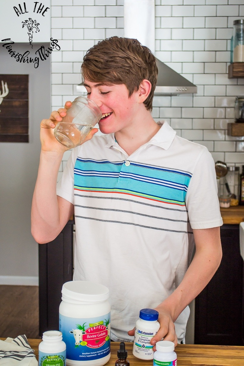 teen boy in white striped shirt drinking water from a Mason jar taking supplements for teenagers