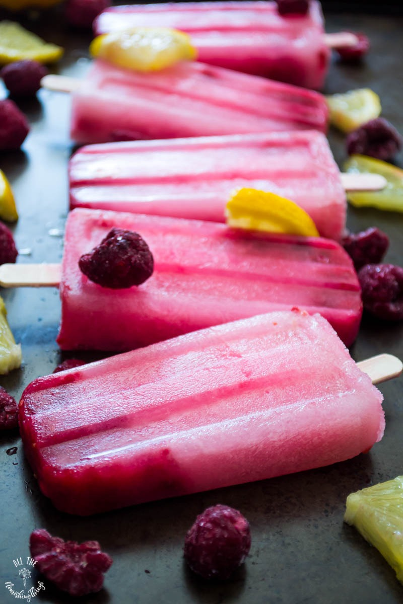 5 bright pink keto raspberry lemon popsicles with frozen berries and lemon slices on top of the popsicles