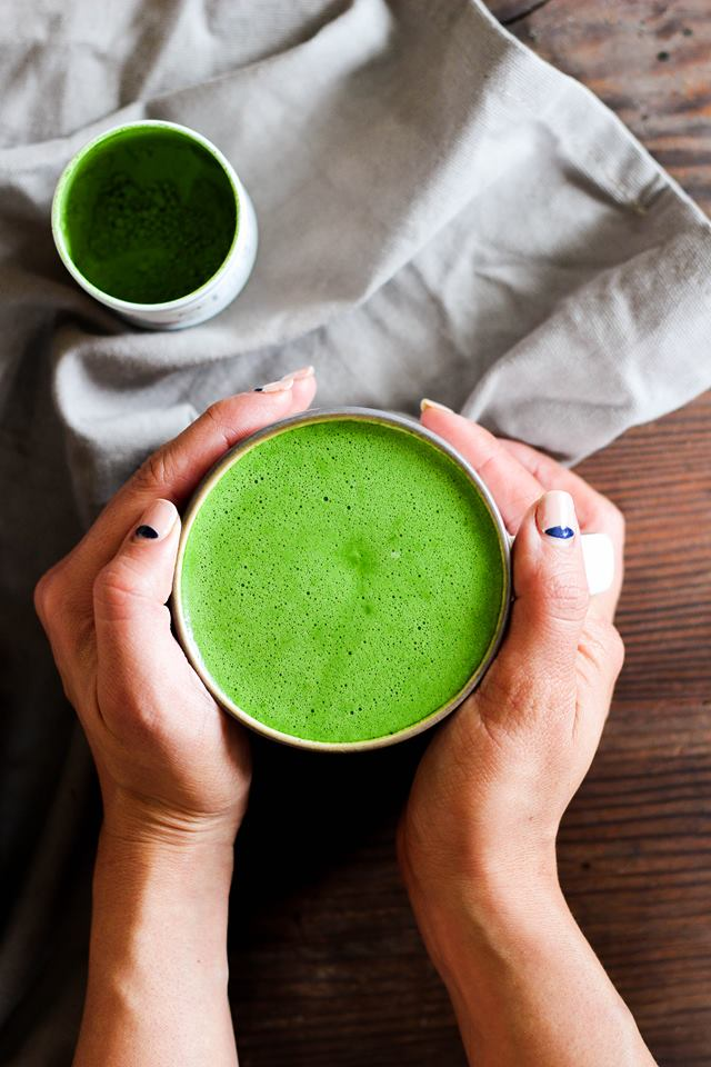 dairy-free matcha latte with mct oil held by hands