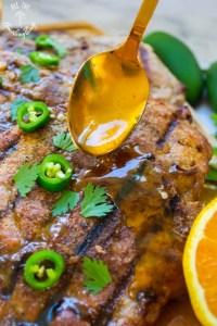 gold spoon of orange-ginger-jalapeno glaze on paleo grilled pork chops