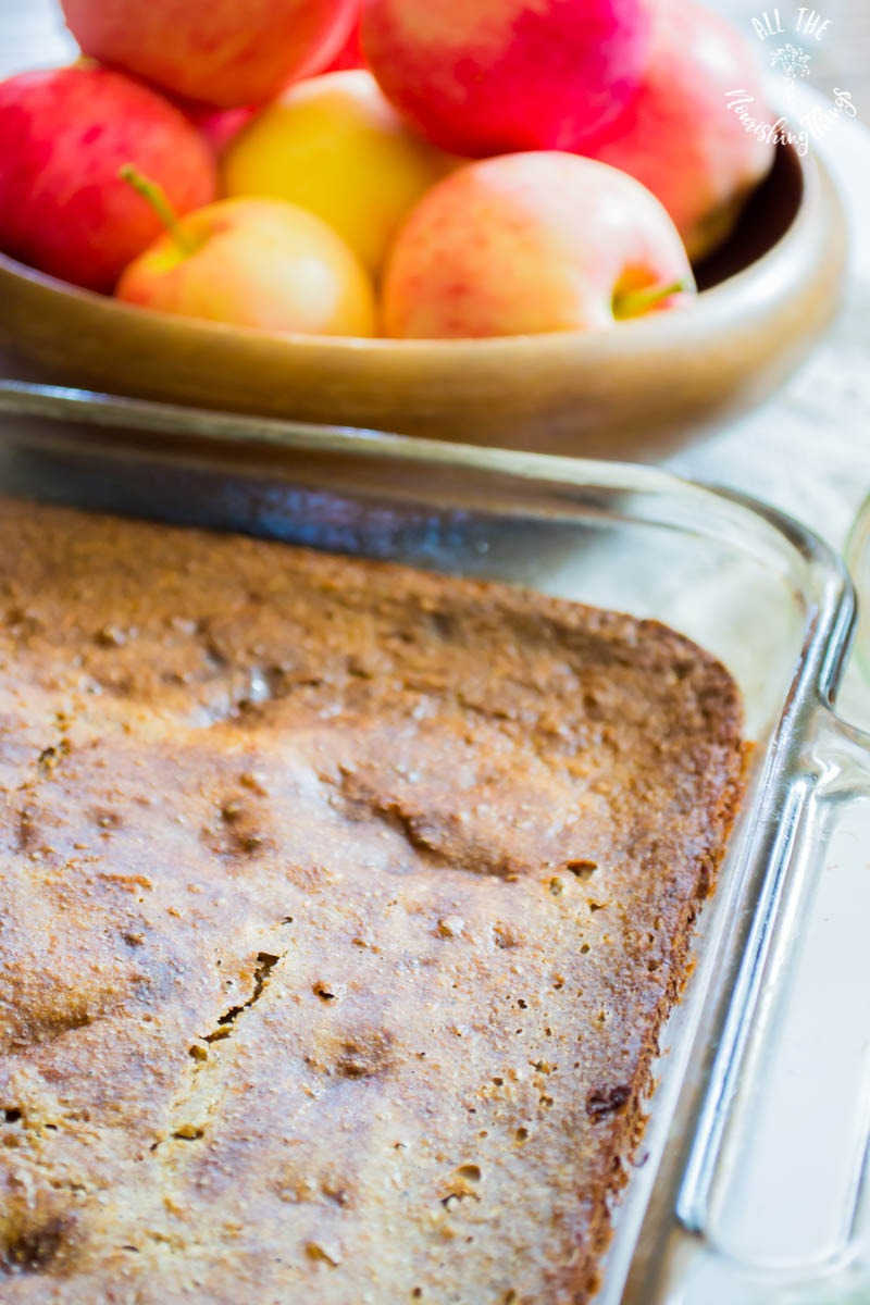 baked apple breakfast cake with bowl of apples