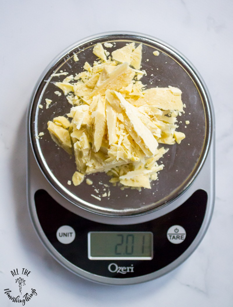 kitchen scale weighing chunks of cacao butter