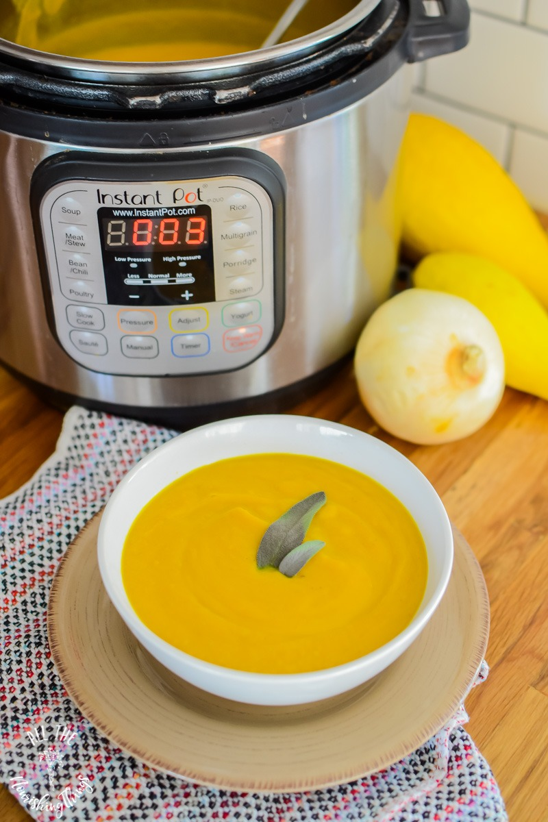 yellow instant pot blended soup garnished with fresh sage