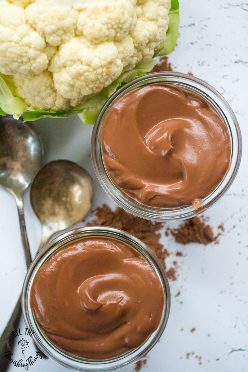 2 jars of paleo cauliflower chocolate pudding with whole head of cauliflower and 2 spoons