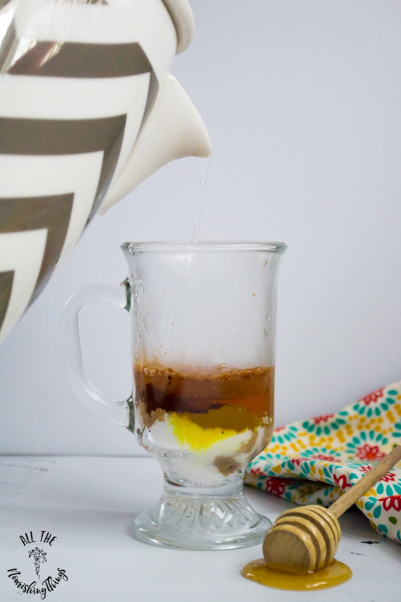 ceramic tea kettle pouring water into a clear mug to make instant paleo golden milk