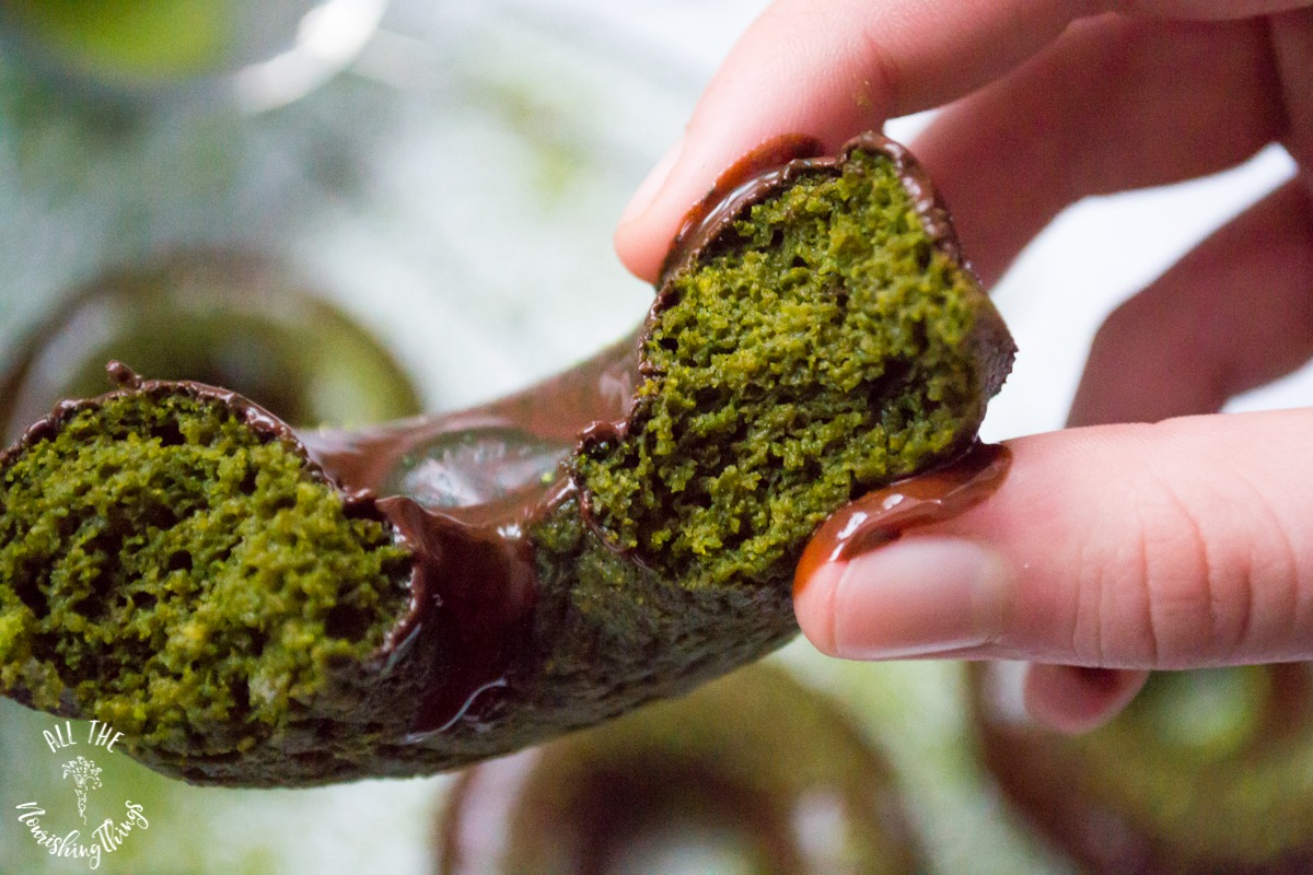 hand holding half of a green keto matcha-moringa baked donut with chocolate glaze