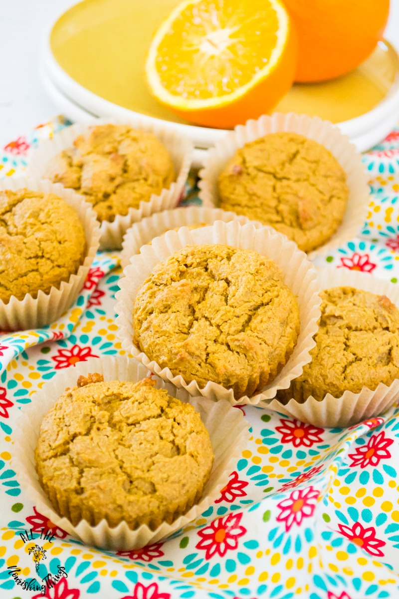 paleo orange muffins in paper liners on a colorful dish towel