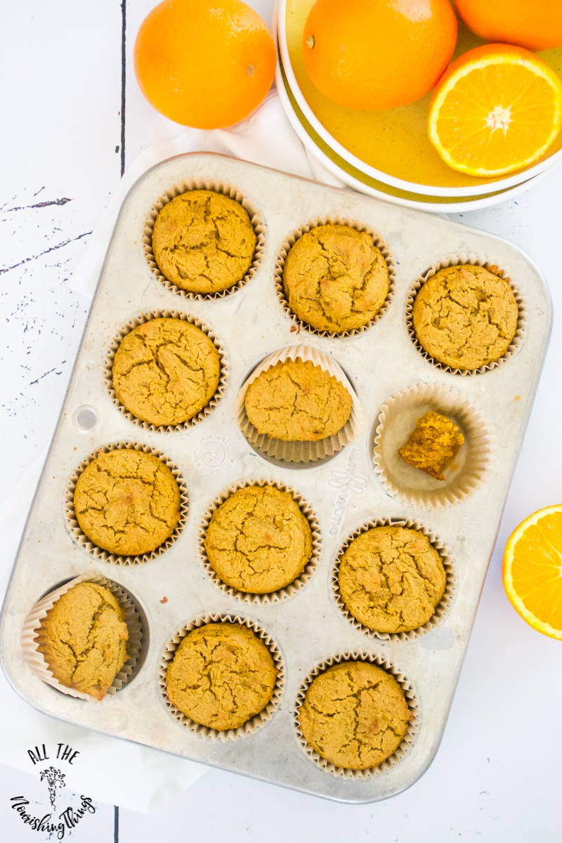 paleo orange muffins in muffin tin with oranges at the top of the photo