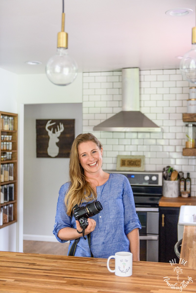 woman holding a camera and standing in her kitchen