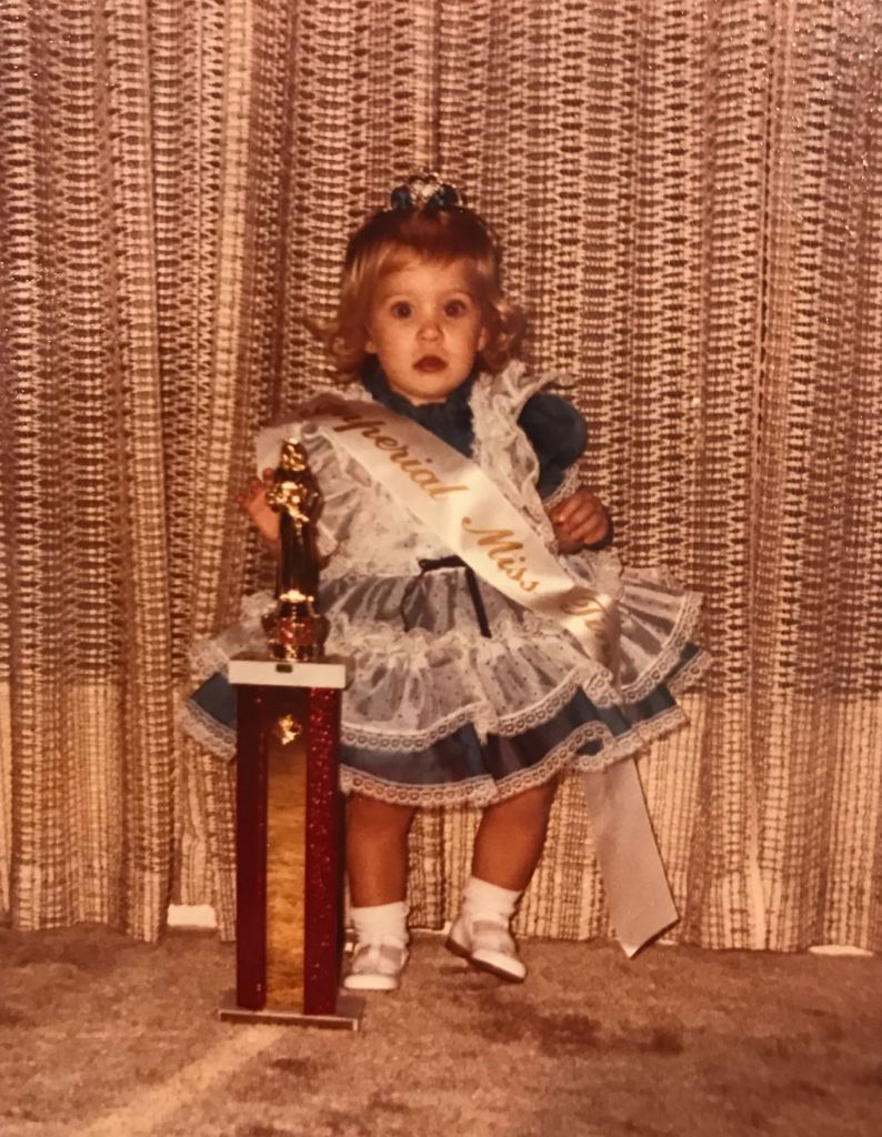 toddler wearing a frilly dress with a trophy