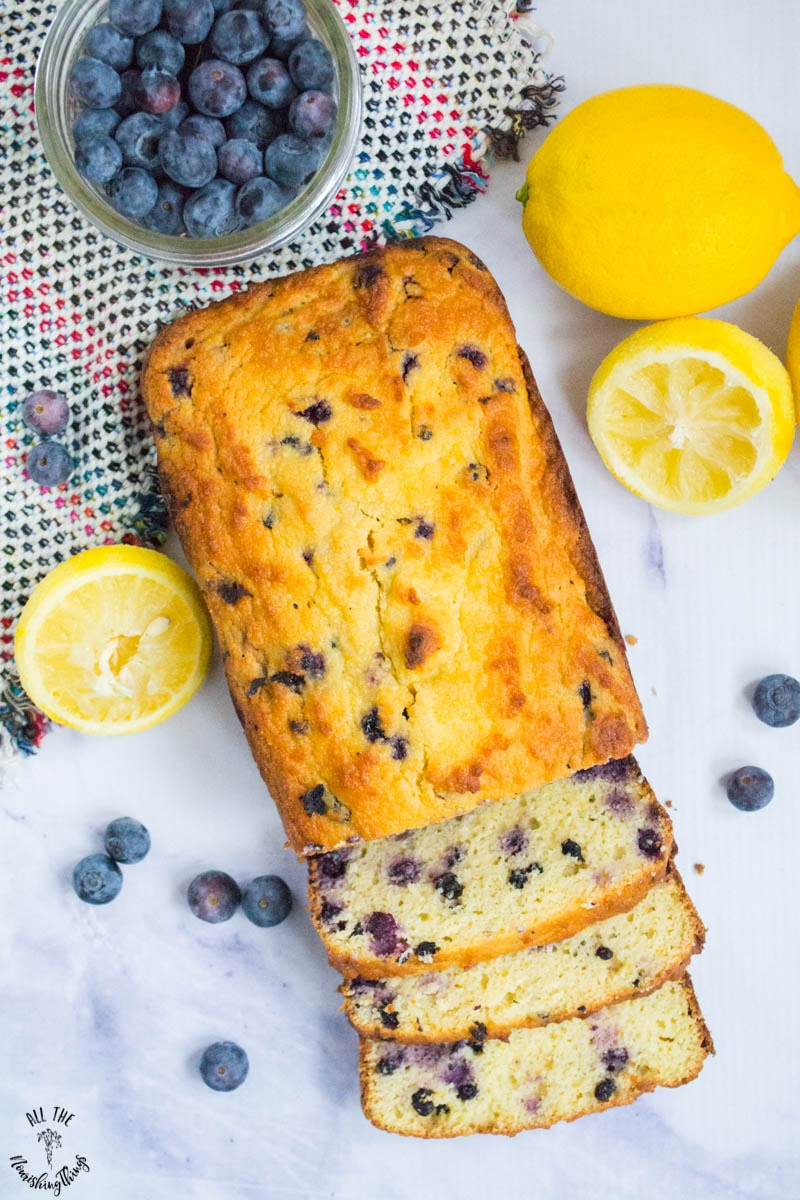 overhead view of keto lemon blueberry bread surrounded by lemons and blueberries