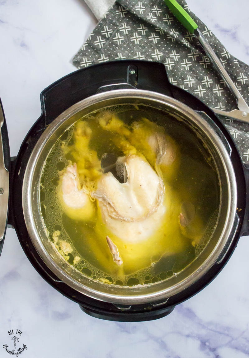 cooked whole chicken in meat broth inside an Instant Pot