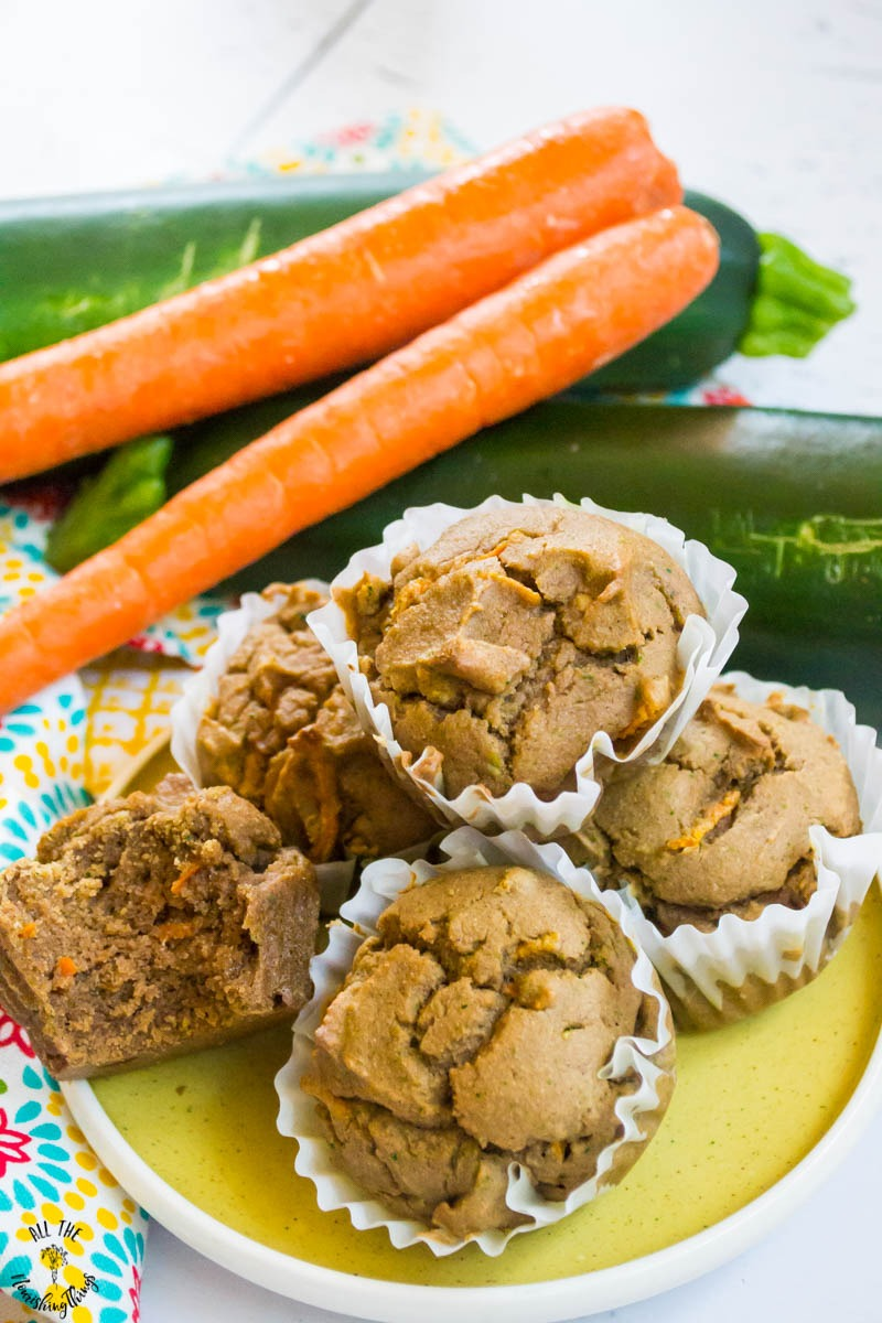 Plate of cassava flour carrot zucchini muffins with carrot and zucchini in the background