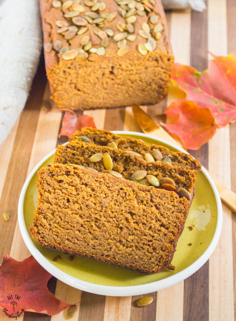3 slices of cassava flour pumpkin bread on a green plate with the whole loaf in the background