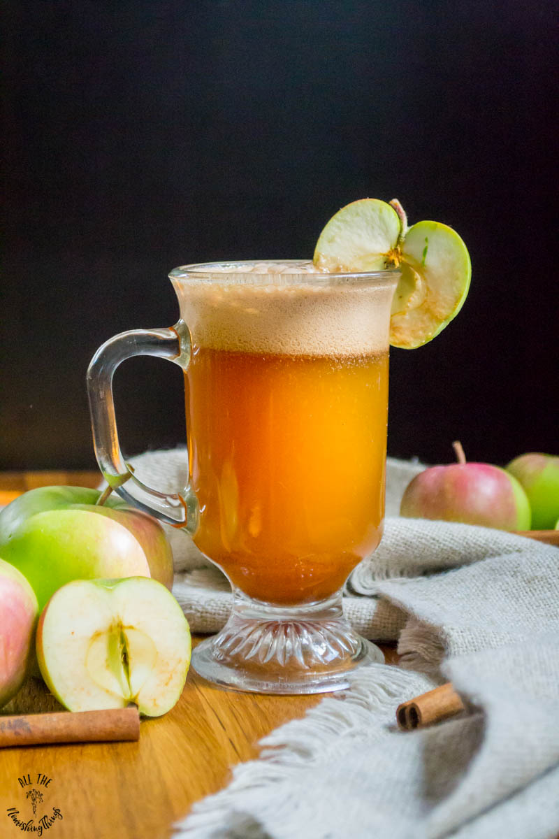 mug of real food copycat starbuck's caramel apple spice with apples and cinnamon sticks