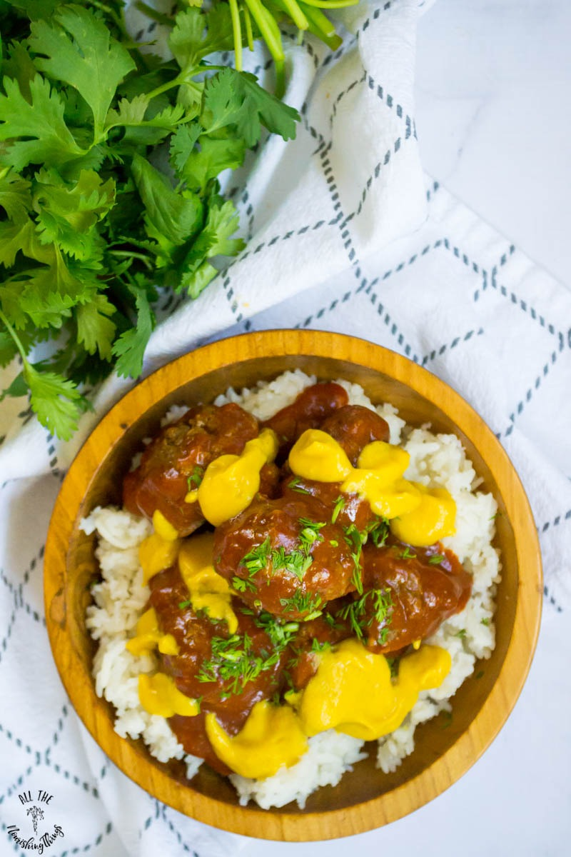 instant pot beef enchilada meatballs served over white rice in a wooden bowl with fresh cilantro and a white and grey towel