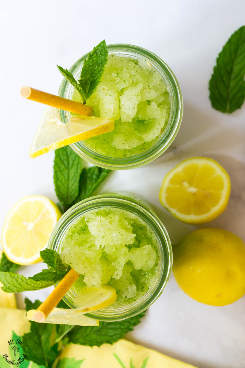 2 glasses of slushy frozen mint lemonade garnished with mint leaves and lemons