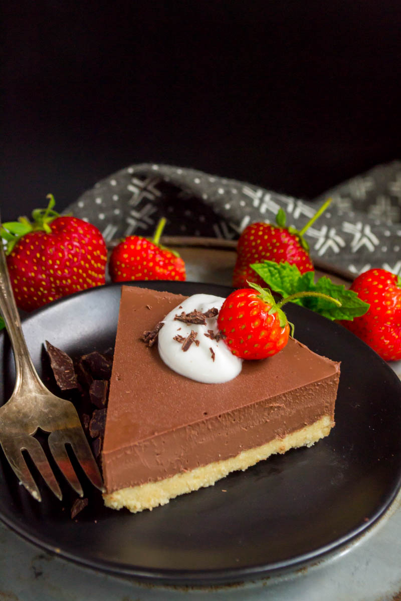 slice of vegan no-bake chocolate pie on a black plate garnished with cream and fresh strawberries and an antique fork