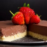 a vegan no-bake chocolate pie with a slice missing from it that is topped with 3 fresh strawberries