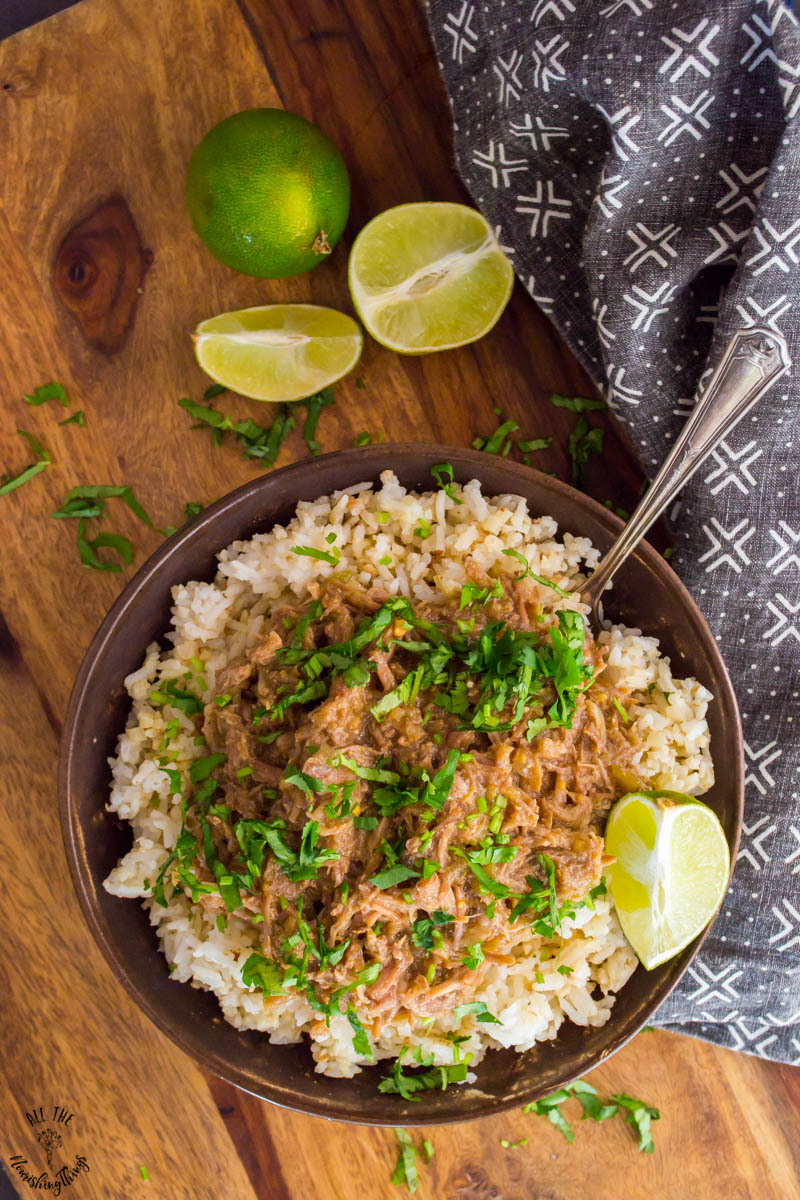 bowl of instant pot green chile pork on a wooden surface with a black and white towel next to the bowl. the pork is topped with fresh cilantro and a fork is inserted in the rice.