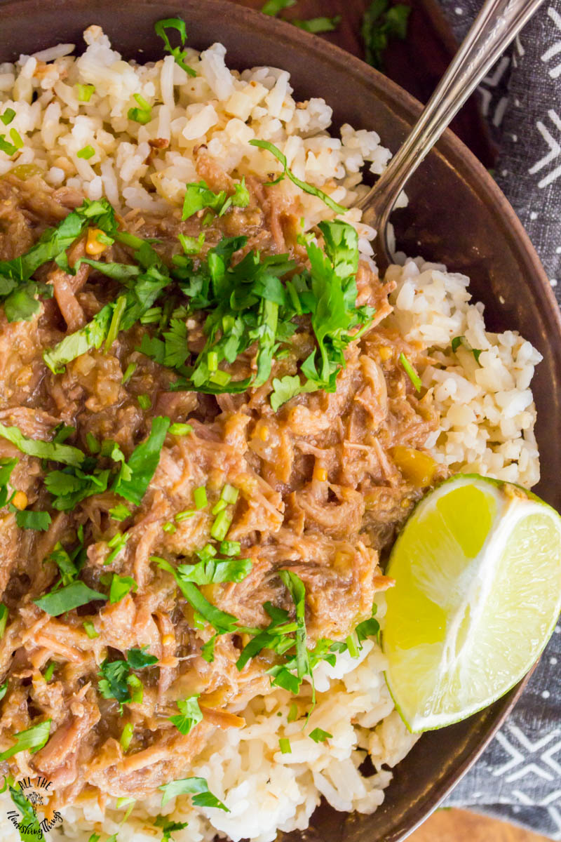 close-up of instant pot green chile pulled pork topped with fresh cilantro and a lime wedge