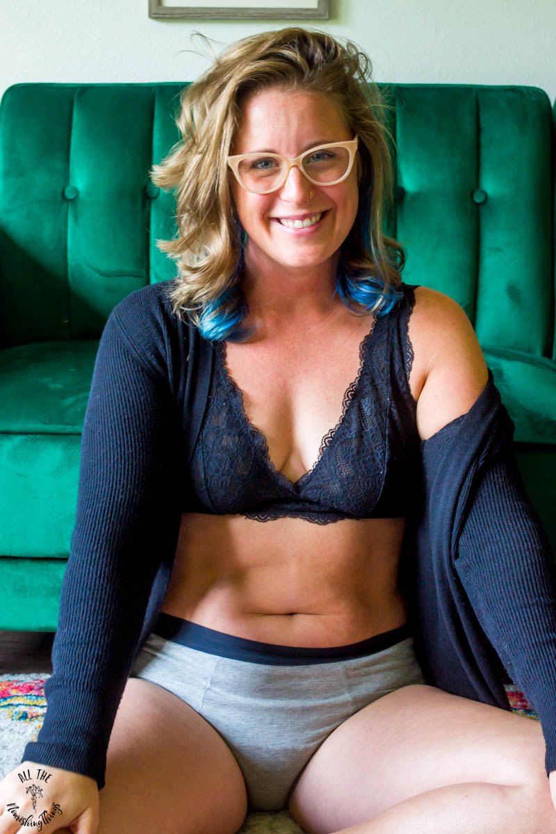 lindsey lockett smiling really big while wearing a black bra and grey period panties