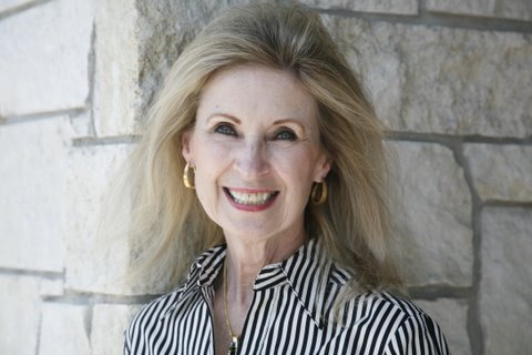 The author's headshot; she is middle-aged, wears a striped shirt, gold earrings, and her hair is long and blonde