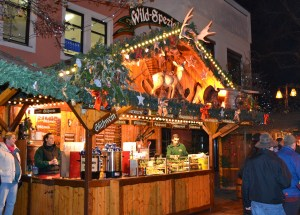 An outdoor kiosk decorated for Christmas is selling drinks and snacks.