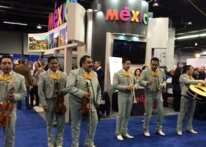 Six mariachi musicians standing in front of a sign that says Mexico